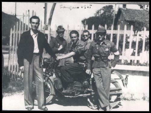 Anonimo, Sangano (To). Nel gruppo di partigiani appartenenti alla 43ª Divisione autonoma De Vitis, primo da destra, appoggiato alla motocicletta, si riconosce Guido Quazza., 1945, CC BY-NC-SA