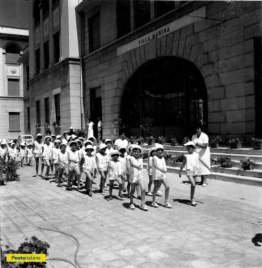 1961, Pesaro. Ordinatamente in fila, si rientra dalla spiaggia alla colonia estiva di Villa Marina, CC BY-NC-ND