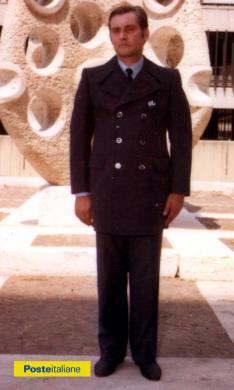 Impiegato posa davanti scultura dell'artista Antonino Virduzzo, nel piazzale del Ministero delle Poste e Telecomunicazioni dell'Eur, indossando la nuova divisa (1980), CC BY-NC-ND